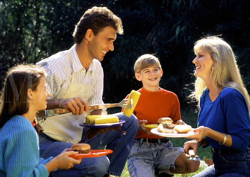 A smiling family eating a picnic.