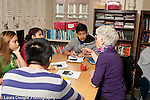 High school classroom female teacher discussing class work with group at table