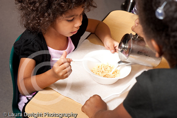 Education preschool meal breakfast girl pouring milk on cereal for friend skills