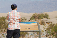 Park visitor stops to read an interpretive sign at Mesquite Flat sand dunes, which features a photo of a sidewinder by wildlife photographer Dan Suzio. Death Valley National Park, California