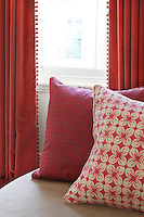Detail of cushions with patterned covers and curtains edged with pompoms in shades of red
