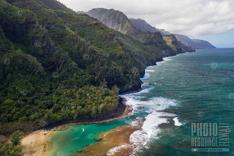 An aerial view of Tunnels Beach, Ha'ena, and the coastline in northern Kaua'i; Mount Makana (nicknamed Bali Hai) is on the right of the mountain range.
