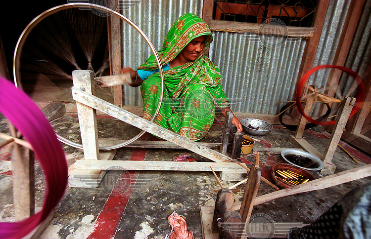 """Sufia Begum turns the wheel of her handloom. She runs a small sari business with the money she borrowed. Grameen Bank, literally meaning """"Bank of the Villages"""", is a microfinance organisation and community development bank that issues small loans without requiring collateral. In 2006 Grameen Bank, along with its founder Dr. Mohammad Yunus, were jointly awarded the Nobel Peace Prize """"for their efforts to create economic and social development from below."""".."""