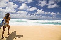 Local Asian woman with surfboard walking down Ehukai Beach to go surfing