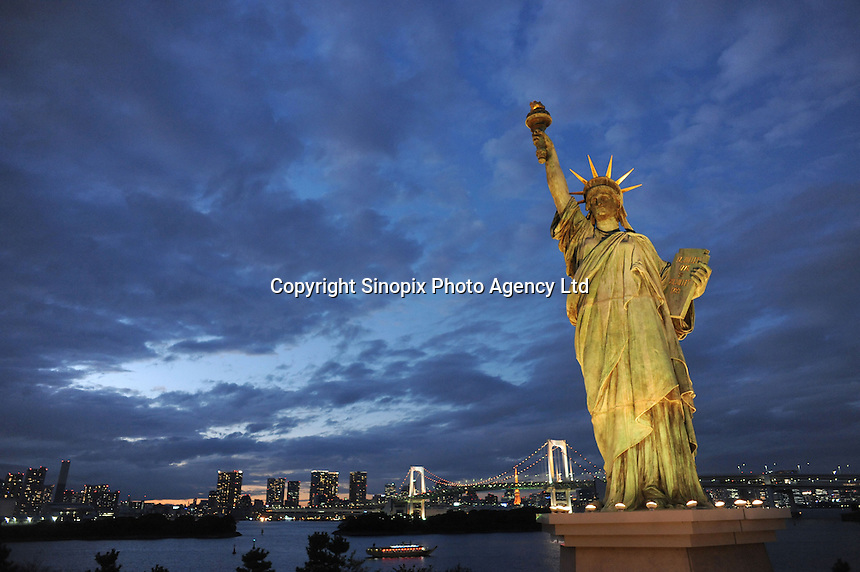 'Statue of Liberty' overlooking  the Rainbow Bridge in Tokyo Bay, Japan. The French Statue of Liberty came to Odaiba, the beach area of Tokyo since April 1998 until May 1999 in commemoration of 'The French year in Japan'. Because of its popularity, in 2000, a replica of the French Statue of Liberty was erected at the same place..23 Nov 2010