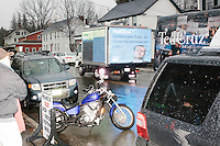 """A mobile animated billboard featuring ads critical of Ted Cruz and his campaign donors drives past his campaign bus and a crowd waiting for Texas senator and Republican presidential candidate Ted Cruz before he speaks at The Village Trestle restaurant in Goffstown, New Hampshire, on Wed., Feb. 3, 2016. The billboard is part of a series of """"stunts"""" put on by the anti-corruption campaign Represent.Us."""