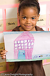 Education preschool 4-5 year olds art activity proud girl holding up picture she drew of a house and fish in a pond vertical