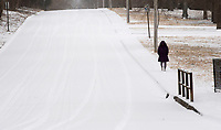 A pedestrian walks along Block Ave. covered in snow Sunday Feb. 14, 2021 in Walker park in Fayetteville. Bitter cold temperatures and more snow is in the forecast according the the National Weather Service. Visit nwaonline.com/210215Daily/ and nwadg.com/photos. (NWA Democrat-Gazette/J.T. Wampler)