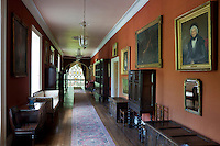 A long corridor lined with antique furniture and family portraits