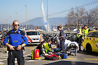 Switzerland. Geneva. Paquis neighborhood. A police officer stands close to an emergency team after a bike accident on the Bergues' Quay. A wounded teenager on stretcher, doctor and paramedics at work. The elegant Geneva Water Fountain (Jet d'Eau de Genève) is the lakeshore's star attraction dazzling visitors as it shoots 140 metres into the sky. 16.03.12 © 2012 Didier Ruef..