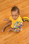 10 month old baby boy sitting shaking toy that rattles