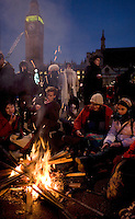 Protestors sit around a fire to keep warm on Parliament Square outside the Houses of Parliament during a student demonstration in Westminster, central London on the day the government passed a bill to increase university tuition fees.
