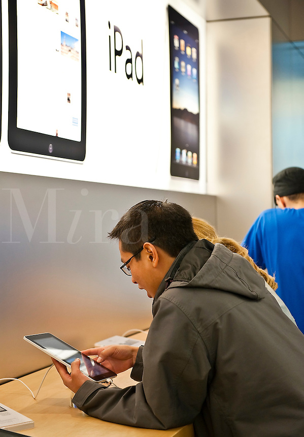 Customers explore the iPad in an Apple store on launch day, Cherry Hill Mall, NJ, USA. April, 3, 2010
