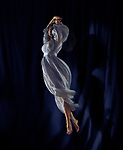 Beautiful young woman dancer in a light blue flowy dress spinning gracefully in the air in a spotlight with a black blue stage curtain in the background Image © MaximImages, License at https://www.maximimages.com