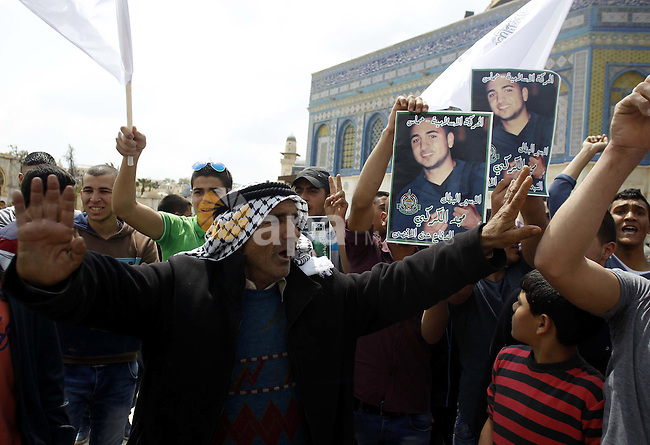 Palestinians shout slogans during a rally marking Palestinian Prisoner Day outside Jerusalem's Dome of the Rock mosque at the Al-Aqsa mosque compound, in Jerusalem's old city, on April 17, 2015. The current number of Palestinians held in Israeli prisons is at least 6,200 and is the biggest for at least five years, according to figures from rights groups. Photo by Saeb Awad