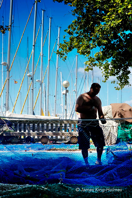 Fishermen in the Bay area of Palma de Mallorca, Spain mend their fishing nets at the harbour-side.