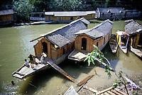 Children playing near houseboats in the Dal Lake, Srinagar, Kashmir, India.