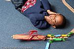 Educaton preschool 4-5 year olds portrait of boy holding palms of hands to cheeks lying on floor near train track and train set horizontal