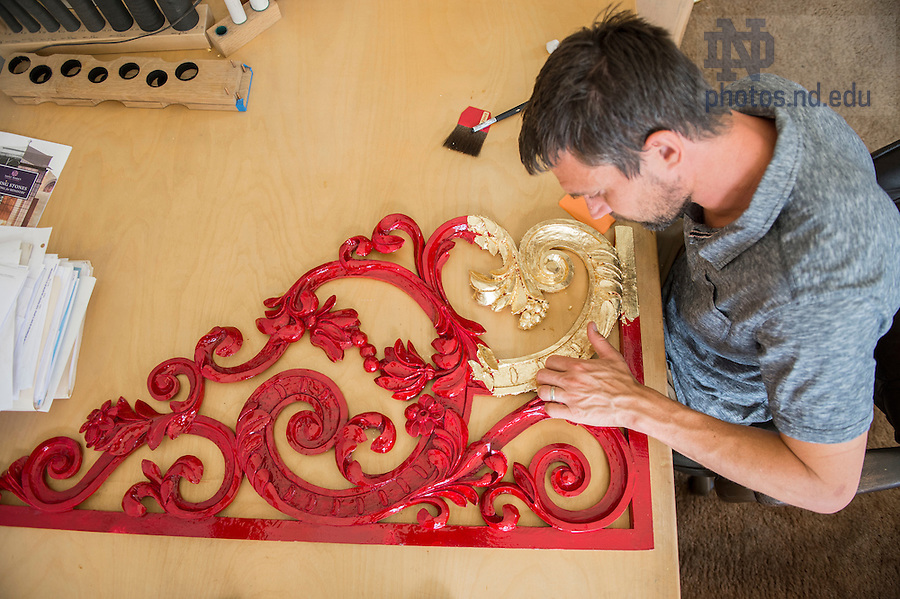 """Andreas Schonger applies 23-karat gold leaf or """"gilding"""" to a segment of decorative screen carved for the basilica organ project by a woodworker in Germany."""