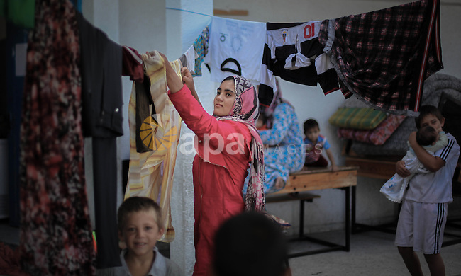 """A Palestinian girl hangs clothes at UN school in Gaza City where she took refuge, on July 17, 2014, a day after the Israeli army warned some 100,000 Palestinians in the eastern Gaza Strip to evacuate their homes. An Israeli official said the Jewish state had agreed a ceasefire with Hamas that will begin at 0300 GMT on July 18, but the Islamist movement said it had """"no information"""" on a deal. Photo by Ezz Zanoun"""