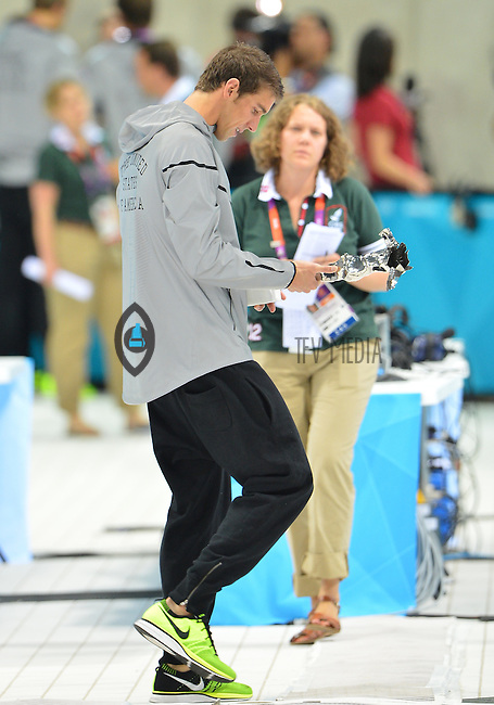 """August 04, 2012..Michael Phelps looks at """"The Greatest Olympic Athlete of All Times"""" trophy awarded to him by FINA as he walks out of the Aquatics Center after competing in the last event of his illustrious career on day eight of 2012 Olympic Games in London, United Kingdom."""