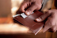 businessman holding a wallet with $100 dollar bills.