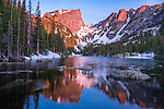 sunrise reflection of Hallett Peak and craggy spires on Flattop Mountain from the shore of Dream Lake, June morning in Rocky Mountain National Park, Colorado, USA