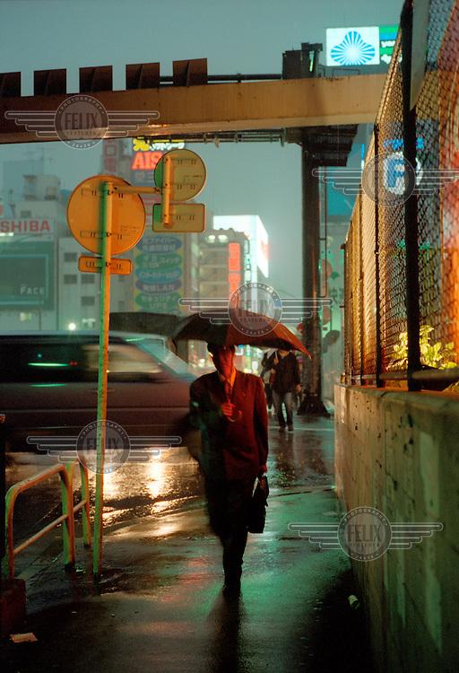 A business commuter with an umbrella walking through the rain.