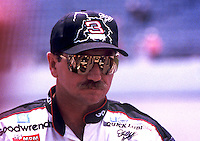 Dale Earnhardt's car is reflected in his sunglasses as he waits to qualify at daytona, July 1996.  (Photo by Brian Cleary/www.bcpix.com)