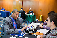 Shevon Morrison, a Navy veteran from Westchester, New York, fills out contact information on an iPad with Uber representatives who asked not to be named at the Recovering Warrior Employment Conference at the Back Bay Event Center in Boston, Massachusetts, USA. Morrison said that the Boston Fire Department job opportunities sounded the most promising because they most closely matched his technical skills.  The employment conference was organized by Hiring Our Heroes and Wounded Warrior Project. Hiring Our Heroes is an initiative of the US Chamber of Commerce Foundation. Approximately 40 veterans registered for the event, during which they had interviews with a number of different regional and national employers, including GE, Bank of America, Uber, and others.