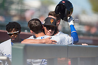 Surprise Saguaros infielder Cole Tucker (2), of the Pittsburgh Pirates organization, hugs Cavan Biggio (26), of the Toronto Blue Jays organization, after Biggio's first home run of the season during an Arizona Fall League game against the Scottsdale Scorpions at Scottsdale Stadium on October 26, 2018 in Scottsdale, Arizona. Surprise defeated Scottsdale 3-1. (Zachary Lucy/Four Seam Images)