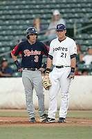 Dustin Ackley #3  of the Tacoma Rainiers talks with Anthony Rizzo #21 of the Tucson Padres after reaching first base in a Pacific Coast League game at Kino Stadium on June 4, 2011  in Tucson, Arizona. .Photo by:  Bill Mitchell/Four Seam Images.