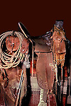 Cowboy western saddle and rawhide rope, antique bit, and custom made pouch