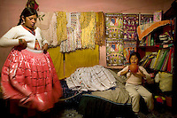 26 year old wrestler Yolanda La Amorosa (fighting name), Veraluz Cortez (real name), left, folds polleras (traditional dresses) in her room with her daughter. Veraluz is a Cholita, a wrestler of native Aymara descent. When Cholitas fight they wear traditional costume. Veraluz fights with the lucha libre (free wrestling) group Los Diosas del Ring. .