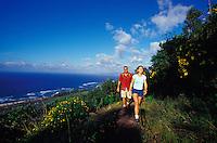 Happy couple enjoying hiking on Kealia Trail, with North Shore ocean in background, Mokuleia,  near Haleiwa, Oahu, Hawaii