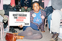"""Ebony Ellise, of Houston, Tex., holds a sign reading """"Don't Believe the Liberal Media,"""" as Texas senator and Republican presidential candidate Ted Cruz speaks at a town hall at Crossing Life Church in Windham, New Hampshire, on Tues. Feb. 2, 2016. The day before, Cruz won the Iowa caucus."""