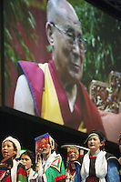 """Switzerland. Basel. St. Jakobshalle. A group of tibetan women dressed in traditional clothings and His Holiness the Dalai Lama. The 14th and current Dalai Lama is Tenzin Gyatso, recognized since 1950. He is the current Dalai Lama, as well as the longest-lived incumbent, well known for his lifelong advocacy for Tibetans inside and outside Tibet. Dalai Lamas are amongst the head monks of the Gelug school, the newest of the schools of Tibetan Buddhism. The Dalai Lama, also called """" Ocean of Wisdom"""" is considered as the incarnation of Chenresi, the Bodhisattva of compassion who is also the protective deity of Tibet. The man in front is a tibetan man working as a body and security man for the Dalai Lama. 8.02.2015 © 2015 Didier Ruef"""