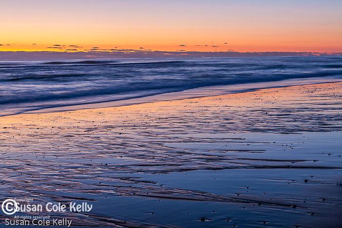 Sunrise paints sand patterns and waves at Coast Guard Beach, Cape Cod National Seashore, Eastham, MA, USA