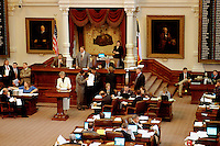 "State government. Texas Legislature. 76th Legislative session. House Speaker James E ""Pete"" Laney (in grey suit on dais). Woman Legislator reads a bill before assembly. Austin Texas."