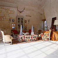 An eclectic mixture of Louis XVI chairs, Islamic textiles and assorted objects has been used to furnish one end of the double-height barn