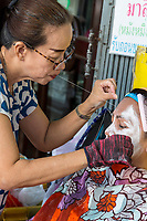 Bangkok, Thailand.  Facial Hair Removal by a Practitioner on the Street in Chinatown.
