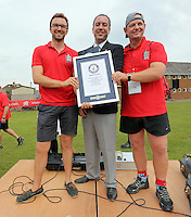 Pictured:Guinness World Records adjudicator Jack Brockbank (C) presents the record certificate to organisers Paul Guest (L) and Mark Marriott (R) in Cardiff, Wales, UK. Wednesday 24 August 2016<br /> Re: The largest rugby scrum has been achieved by Golden Oldies at University Fields in Cardiff south Wales, UK. It was refereed by welsh international referee Nigel Owens. Guinness World Records has verified the new record in which 1297 people took part in.