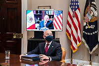United States Secretary of Homeland Security Alejandro Mayorkas  listens as US President Joe Biden participates in a virtual bilateral meeting with President Andrés Manuel López Obrador of Mexico in the Roosevelt Room of the White House in Washington on March 1st, 2021. <br /> Credit: Anna Moneymaker / Pool via CNP /MediaPunch