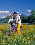 Paar mit Fahrraedern in einer Blumenwiese schauen in Landkarte | couple with bicycles in a flower meadow looking into a map