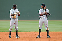 June 14, 2009: Brothers Jeremy Beckham (24), left, and Tim Beckham (26) of the Bowling Green Hot Rods, Class A affiliate of the Tampa Bay Rays, talk during a pitching change in a game against the Greenville Drive at Fluor Field at the West End in Greenville, S.C. Photo by: Tom Priddy/Four Seam Images