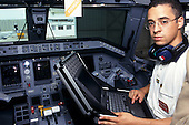 Sao Paulo, Brazil. Technician with Compaq laptop computer checking cockpit functions of a new aircraft at Embraer factory.