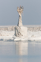 A channel marker in Cleveland Harbor covered by frozen layers of ice.  The marker was encased in ice by crashing waves in frigid air temperatures during mid-December.