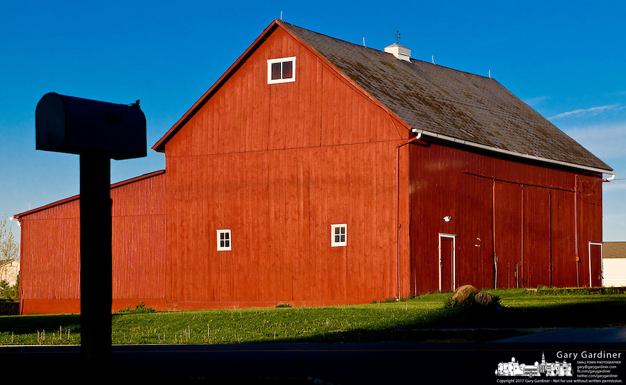 A mailbox is silhouetted against a clear morning sky as sunlight strikes the wall of one of the barns still standing in Westerville, Ohio. Photo Copyright Gary Gardiner.