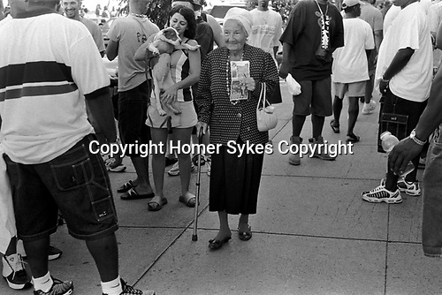 South Beach Ocean Drive, Miami Florida USA 1990s. An older senior woman with walking stick amongst a crowd of young African American men hanging out  1999 US.