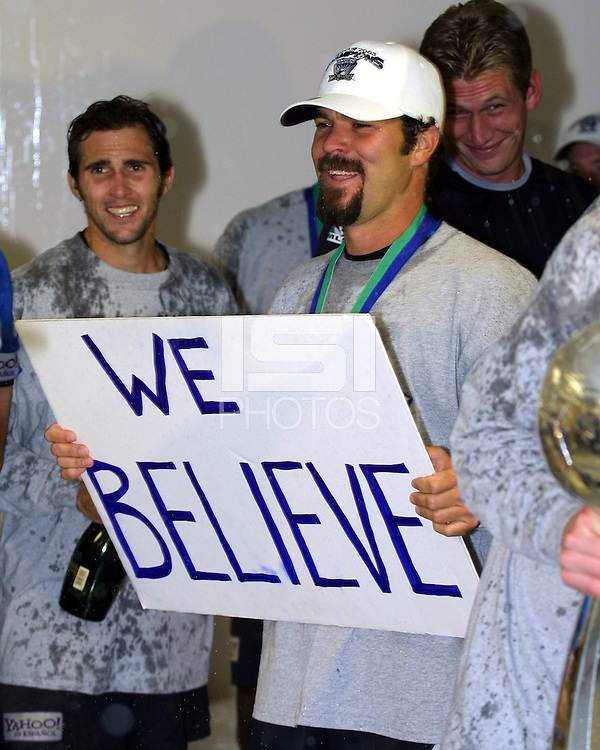 """Troy Dayak holds up the """"We Believe"""" sign that became the team's motto during the 2003 MLS playoffs as Brian Mullan (left) and Josh Saunders (right) look on during the lockerroom postgame celebration.  The San Jose Earthquakes defeated the Chicago Fire 4-2 in the MLS Championship at The Home Depot Center on November 23, 2003."""